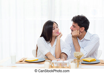Cheerful asian young man and woman having sitting lunch and talking  together at kitchen