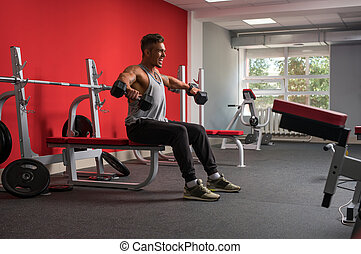 Cheerful athlete exercising with dumbbells in gym