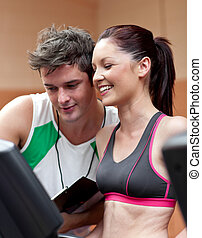 Cheerful athletic woman standing on a running machine with her personal coach in a fitness center