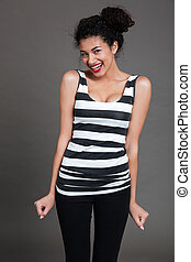 Cheerful attractive african american young woman standing and laughing