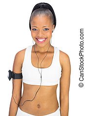 Cheerful attractive woman in sportswear listening to music