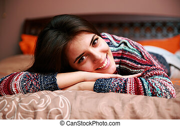 Cheerful attractive woman lying on the bed at home