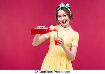 Cheerful attractive woman pouring juice from bottle into the glass