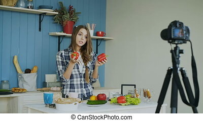 Cheerful attractive woman recording video blog about vegetarian healthy food on dslr camera in kitchen at home