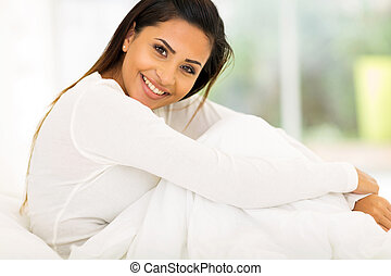 attractive woman sitting on bed at home