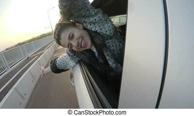 Cheerful attractive woman waving happily from the back seat of a car with her head out the window at sunset