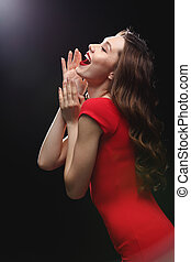 Cheerful attractive young woman in red dress standing and laughing