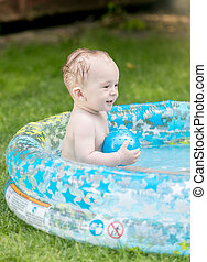 Cheerful baby boy playing in inflatable pool