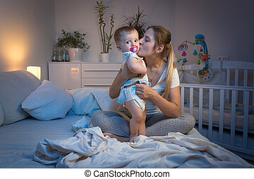 Cheerful baby boy playing with mother on bed at night