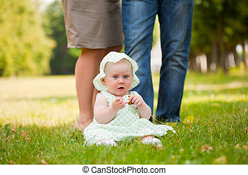 cheerful baby girl is playing on the grass