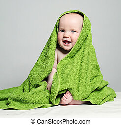 Cheerful Baby in Green Towel on Background. Little Child, 6 month old