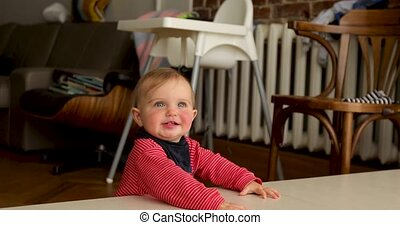 Cheerful baby in living room - Funny toddler smiling while...