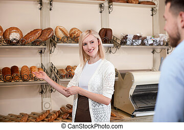 Cheerful baker is proposing wide assortment of pastry