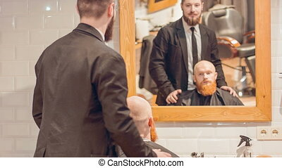 Cheerful barber talking with his client
