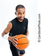 Cheerful basketball player standing with ball