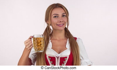 Cheerful Bavarian woman in dirndl dress showing thumbs up...