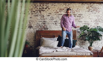 Cheerful bearded guy in jeans and shirt is dancing on double...