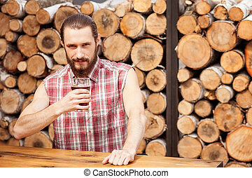 Cheerful bearded guy is resting in bar