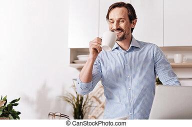 Cheerful bearded man enjoying the weekend at home