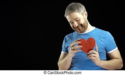 Cheerful bearded man in blue tshirt holds one red heart shape