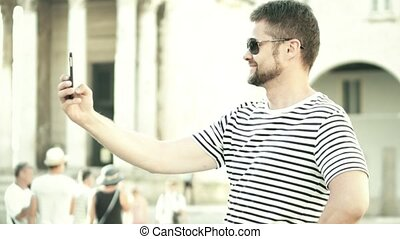 Cheerful bearded man making selfies with his phone on vacation
