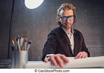 Cheerful bearded man situating at desk near blueprint
