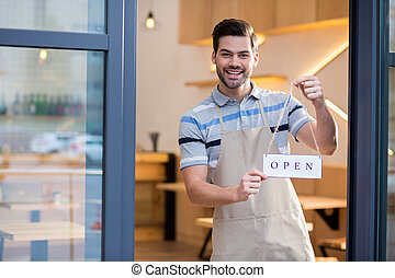Cheerful bearded man standing at the door