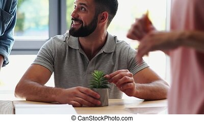 Cheerful bearded man talking with his colleague in the...