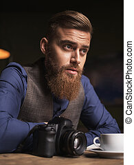 Cheerful bearded photo artist is resting