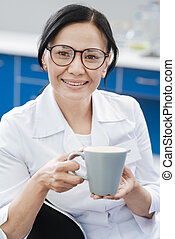 Cheerful beautiful woman holding a cup