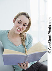 Cheerful beautiful woman reading a book while sitting on couch