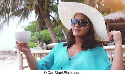 Cheerful beautiful woman wearing hat and sunglasses on holiday, sitting in beach cafe with scenic views of the sea and palm trees drinks tea has a breakfast. slow motion. 3840x2160