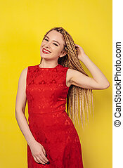 cheerful beautiful young woman dressed in a red dress, holds pigtails.