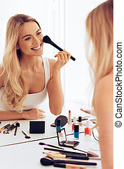 Cheerful beauty. Cheerful young woman applying make-up and looking at her reflection in mirror while sitting at the dressing table
