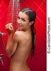 Cheerful beauty in shower. Beautiful young woman taking...