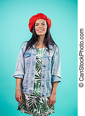 cheerful black-haired woman wearing denim jacket, dress and red beret