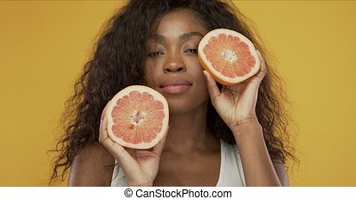 Cheerful black lady showing halves of grapefruit - ...
