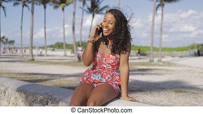 Cheerful black woman speaking on phone outside