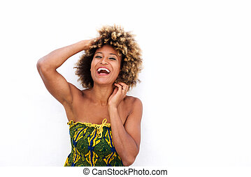 Cheerful black woman standing against white wall