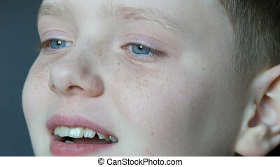Cheerful blond boy with blue eyes and freckles contagiously sincerely laughs