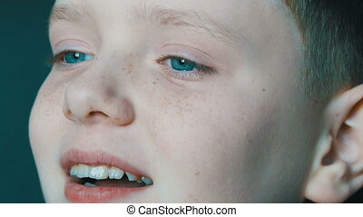 Cheerful blond boy with blue eyes and freckles contagiously...
