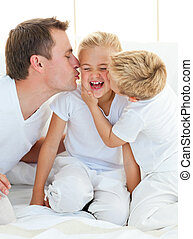 Cheerful blond boy with his father hugging their relative sitting on a bed