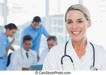 Cheerful blond doctor posing with colleagues in background