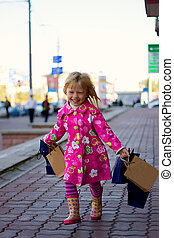 Cheerful blond girl 3 years old with shopping