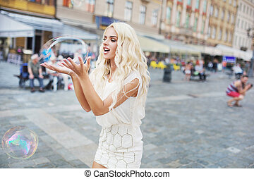 Cheerful blonde carrying huge soap bubble - Cheerful blond...