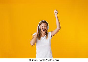 Cheerful blonde girl in headphones dancing and laughing