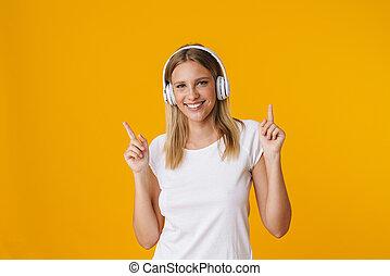 Cheerful blonde girl in headphones pointing fingers upward