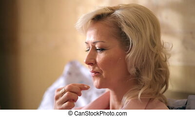 Cheerful blonde woman eating breakfast on a bed.