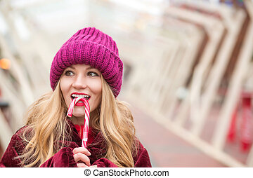 Cheerful blonde woman in red knitted hat posing with candy cane at the street