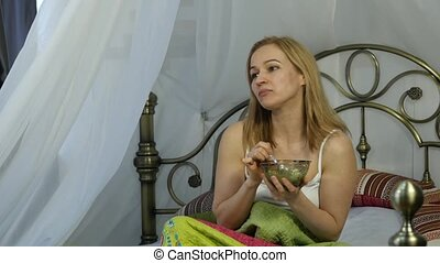 cheerful blonde woman is eating a delicious salad on a bed, healthy breakfast. 4K